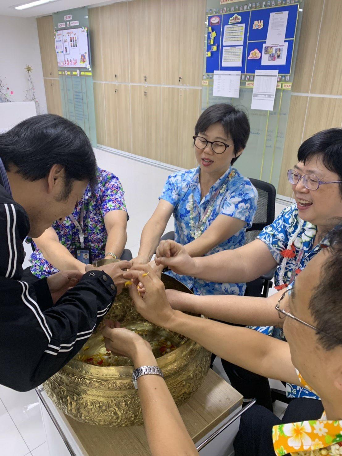 ใช้น้ำสะอาดที่ใส่กลีบดอกไม้รดลงบนฝ่ามืออวยพรให้แก่ผู้อาวุโสไทย