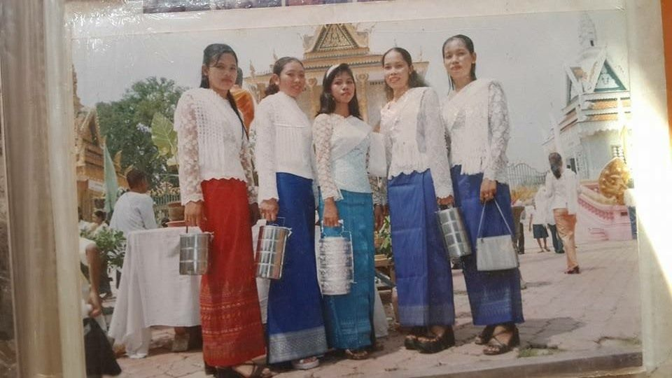Litrato ng mga kababaihan sa harapan ng templo, may handang pagkain at suot ang kanilang tradisyonal na kasuotan sa Kampuchea