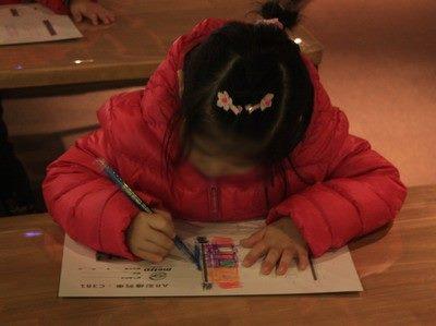 小朋友專注在圖畫紙上彩繪列車