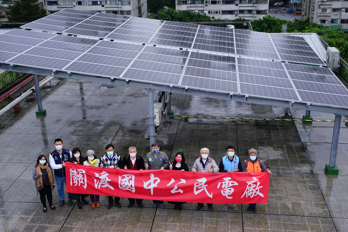 Mayor and dignitaries standing before the solar panels at Guandu Junior High School