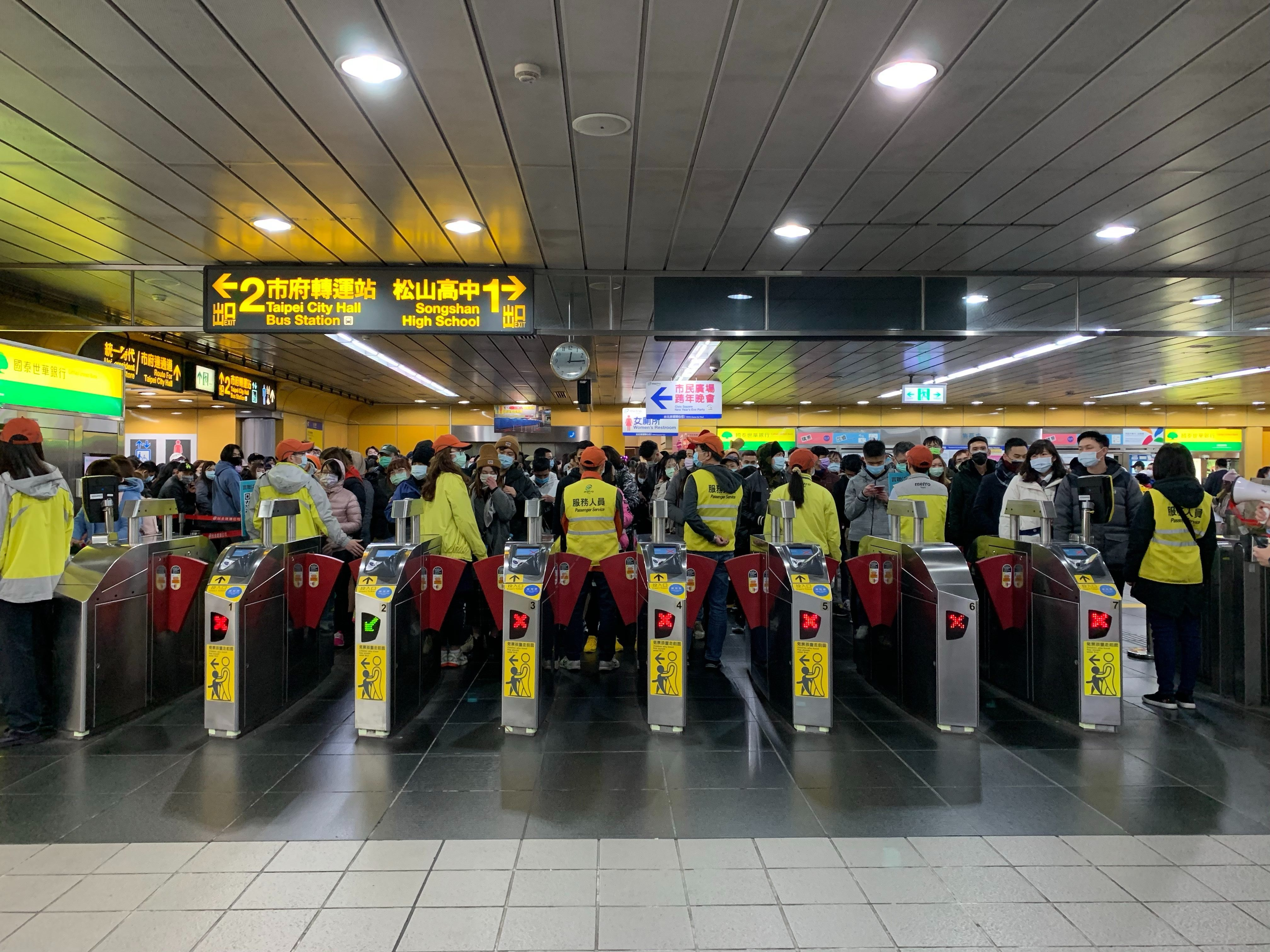 Passengers line up outside the gates at the MRT Station