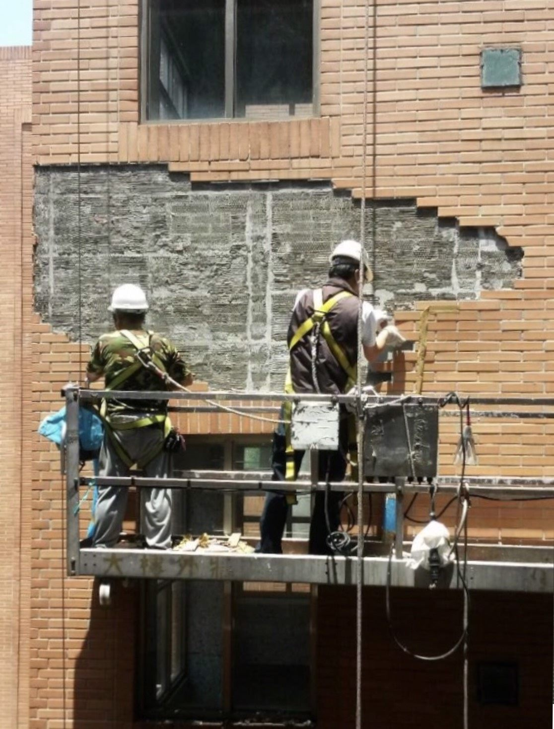Workers repairing damaged building wall surfaces