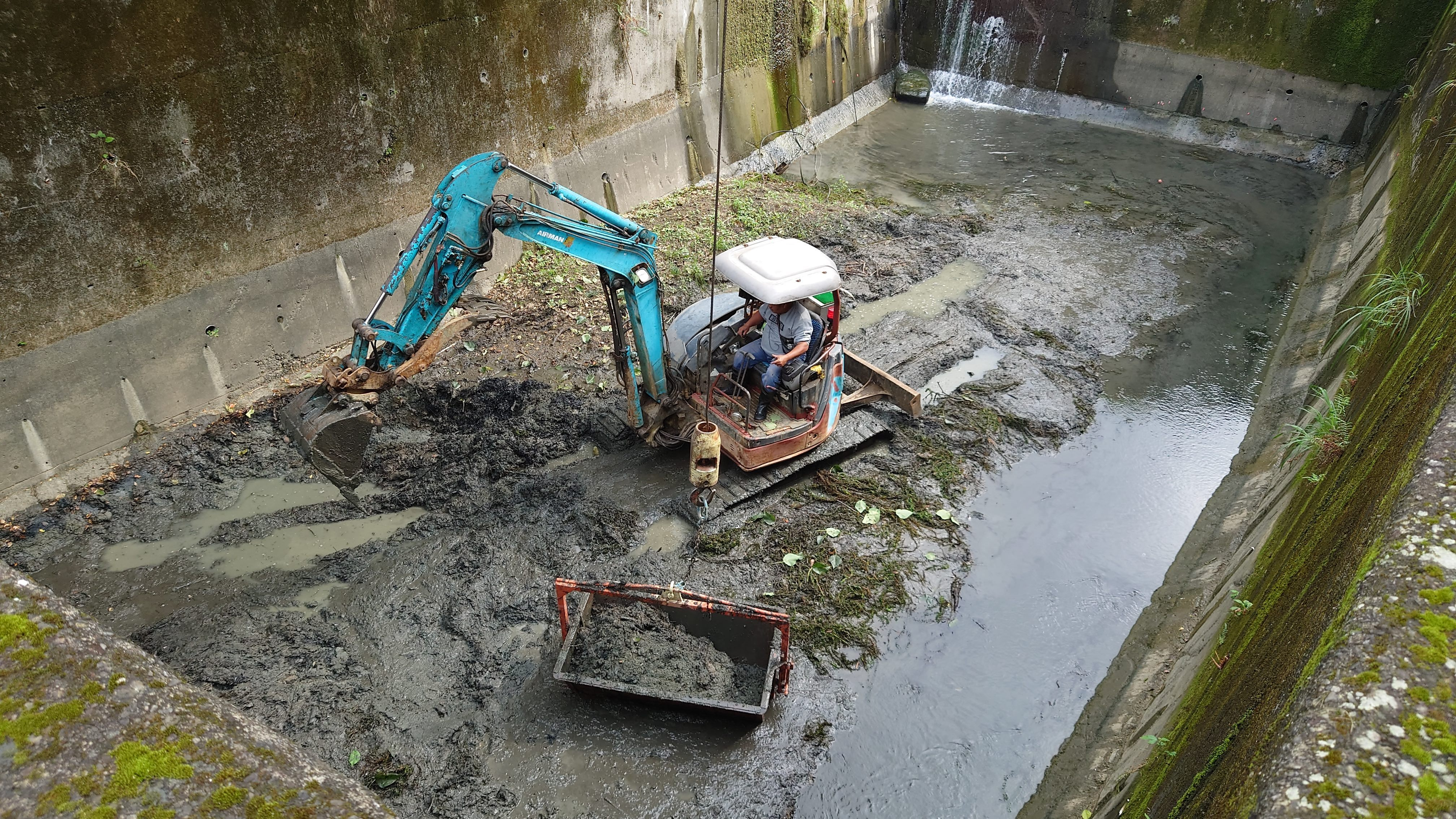 Workers removing muck from a silt detention basin